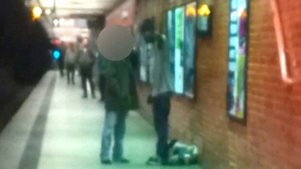 Two men are seen talking on a New York City subway platform in this framegrab from a video released Monday by the New York Police Department. According to police, the man on the right pushed the other man (face blocked), Han Ki-Suck, onto the track.