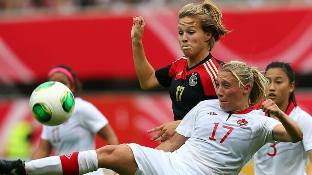 Isabelle Linden (back) of Germany and Canada's Melissa Busque, right, battle for the ball during a women's friendly at Benteler Arena in Paderborn, Germany on Wednesday.