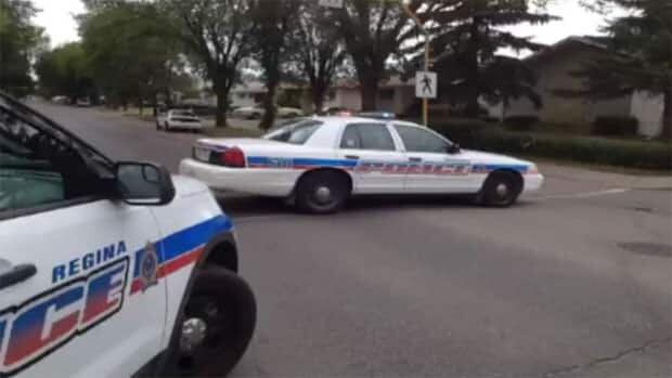 Eleven police cruisers have surrounded a home in northwest Regina where three schools are on lockdown.