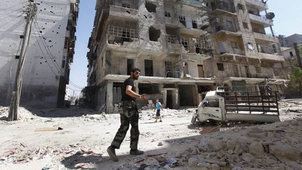 A Free Syrian Army soldier walks next to a destroyed building that was attacked by a Syrian government airstrike in Aleppo city, Syria, on Monday Sept. 24, 2012.