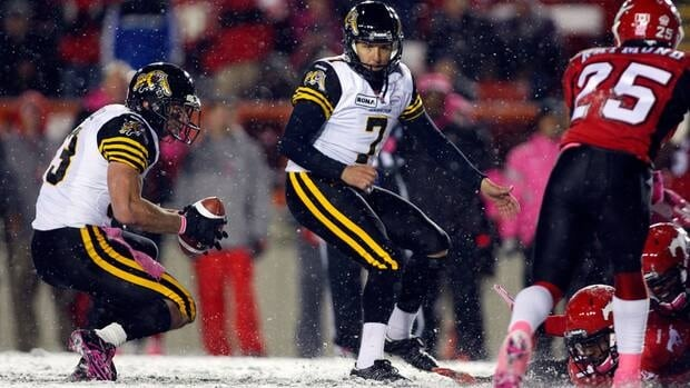 Hamilton Tiger-Cats' Andy Fantuz, left, mishandles the snap as kicker Luca Congi looks on. The ball slipped from Fantuz's fingers and Congi didn't get the kick away.