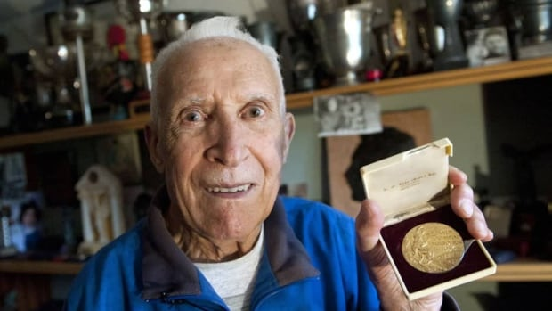Alain Mimoun poses with his Olympic gold medal just prior to his 90th birthday in 2010. Mimoun won four Olympic medals, four world championships and 32 French national titles between 1947 and 1966.