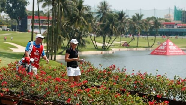 Stacy Lewis and caddie Travis Wilson stroll to the 17th hole at Sentosa Golf Club on Friday.