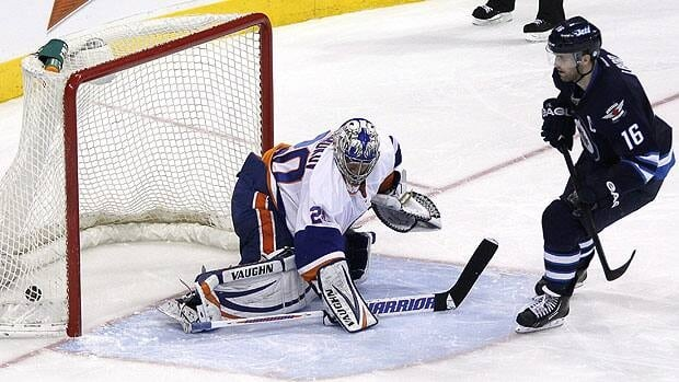 Jets' Andrew Ladd scores on New York Islanders goaltender Evgeni Nabokov during a shootout in Winnipeg on April 20.