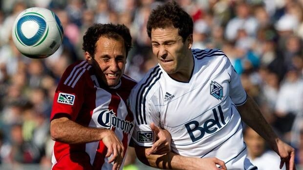 Chivas USA's Nick LaBrocca, left, and Vancouver Whitecaps' Kevin Harmse battle for the ball in a game between the two teams on Apr. 16, 2011.