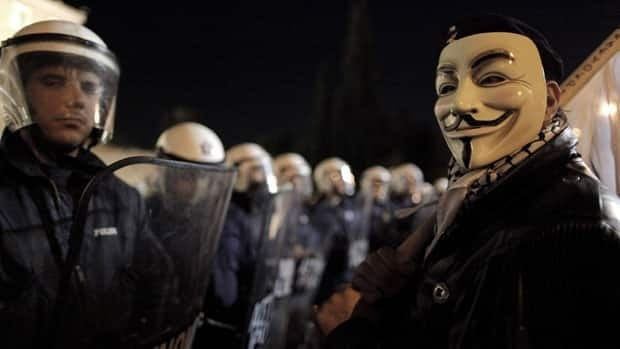 A demonstrator wearing a Guy Fawkes mask stands next to riot police that secure the Greek parliament during an anti- austerity rally in Athens on Sunday.