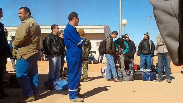 In this photo secretly taken by a hostage, an Islamic militant in camouflage uniform stands among Algerian employees forced to leave their lodging at the In Amenas natural gas complex.  Algeria's prime minister accused a Canadian of co-ordinating last week's raid on the desert gas plant, where more than three dozen mostly foreign hostages were killed.