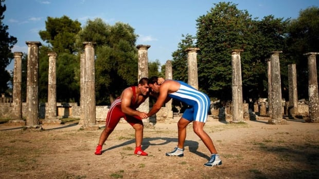Greece's two-time bronze world freestyle wrestling athlete Ioannis Arzoumanidis, left, and Greece's Georgios Koutsioubas, a world champion at men's under 21 Greco-roman wrestling athlete, perform to promote their sport at Palaestra in ancient Olympia, Greece on Sunday.