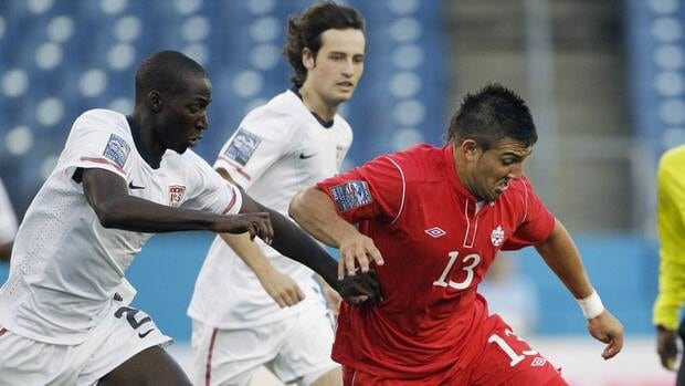 Canada's Lucas Cavallini, right, dribbles the ball as he is defended by Ike Opara, left, and Mix Diskerud, centre, of the United States during the first half on Saturday.