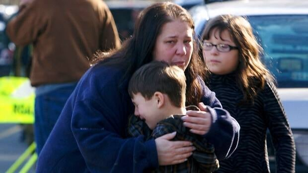 A young boy is comforted outside Sandy Hook Elementary School after a shooting in Newtown, Connecticut, on Friday.