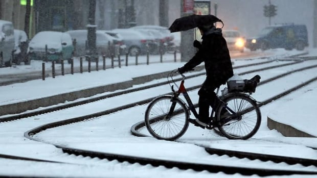 A cyclist holds an umbrella as he crosses tracks during snowfalls in Cologne, Germany. After the snow, many trains from Belgium were cancelled, including some high-speed trains to Germany.