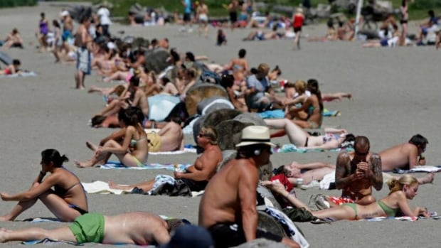 This file photo from 2012 shows sunbathers at English Bay Beach in Vancouver, B.C.  Police say that a 13-year-old girl was targeted at the beach on Wednesday by a man who pestered her for personal information and then exposed his genitals to her.