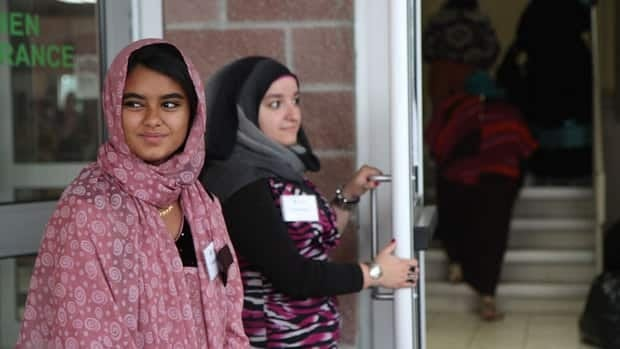 Rimsha Laeek, front, and other volunteers greet visitors to Hamilton Mountain Mosque as they begin prayer sessions to celebrate the end of Ramadan Thursday morning. Laeek, who started observing Ramadan a year ago, says she is proud of herself for going through another month of fasting from dawn to dusk.