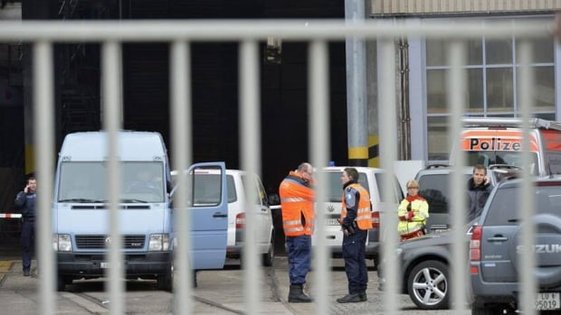 Police stand in front of a wood-processing company in Menznau in central Switzerland on Wednesday, where prosecutors say three people were killed in a shooting.