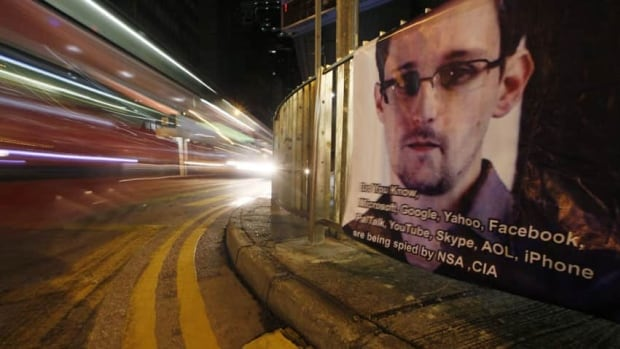 A bus drives past a banner supporting Edward Snowden, a former CIA employee who leaked top-secret documents about sweeping U.S. surveillance programs, at Central, Hong Kong's business district. Snowden has been charged with espionage and theft of government property.