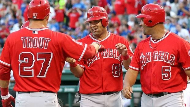 Angels' Kendrys Morales, centre, is congratulated by teammates Mike Trout and Albert Pujols after hitting a grand slam in the 6th inning against the Texas Rangers on Monday.