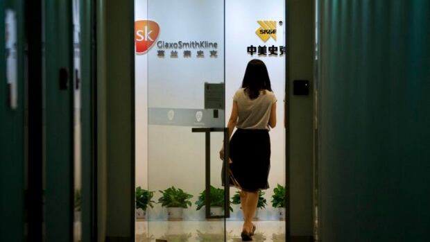 A woman enters an office of GlaxoSimthKline in Beijing, China, Thursday, July 11, 2013. China's police ministry accused executives of pharmaceutical supplier GlaxoSmithKline on Thursday of conducting a large and long-running bribery campaign to persuade doctors to prescribe drugs.