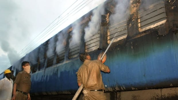 An Indian fire official douses fire coming out from a coach of a passenger train at Nellor, nearly 500 kilometres south of Hyderabad, India.