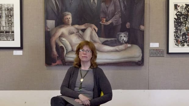 Kingston, Ont., artist Maggie Sutherland sits in front of her painting of Prime Minister Stephen Harper, a piece that spurred a recently dismissed human rights complaint.