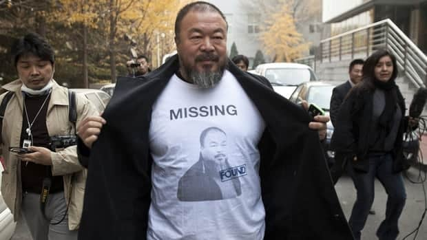 "Chinese dissident artist Ai Weiwei reveals a shirt bearing his portrait as he walks into the Beijing Local Taxation Bureau on Nov. 16, to deal with his conviction for what Chinese authorities say were ""economic crimes."""