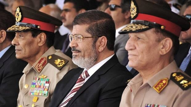President Mohammed Morsi, centre, ordered the return of  Egypt's dissolved parliament, but his defiance against a previous ruling could spark more instability.