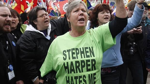 Demonstrators at a May Day rally in Toronto wore shirts with the same slogan as buttons that employees in the public service have gotten into trouble for wearing.