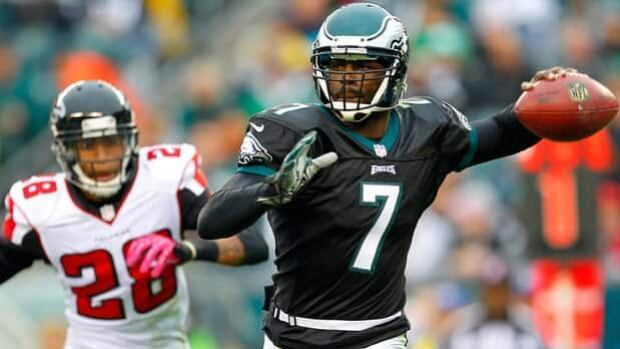 Eagles pivot Michael Vick (7) rolls out to elude Thomas DeCoud in a 30-17 loss to the Falcons.