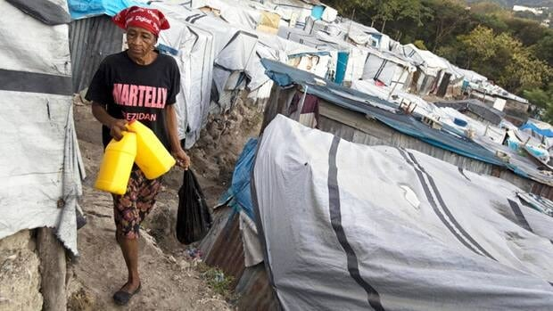 In this Jan. 5, 2012 photo, a woman wears a T-shirt with the name of President Michel Martelly as she walks through the Beaubin camp for people displaced by the 2010 earthquake in Petionville, Haiti.