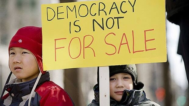 The Auclairs, Pierre-Andre, 7, left, and Ernest, 5, attended a demonstration against the so-called robocalls controversy in Montreal March 11. It has been a little over a year since the first allegations of fraudulent election phone calls in the Ontario riding of Guelph.