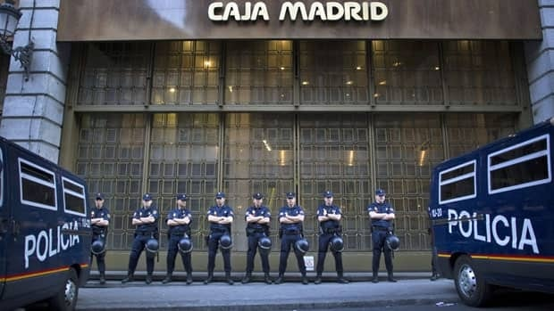Riot police stand guard in front of a bank branch during a protest against foreclosures in Madrid in May. Spain has been offered $125 billion in aid for its troubled banking system.