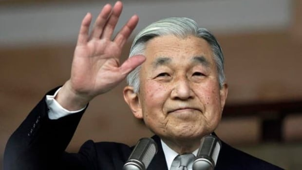 Japan's Emperor Akihito waves to a crowd of well-wishers through the bulletproof glass of a balcony, during a morning appearance to mark his 79th birthday, at the Imperial Palace in Tokyo.