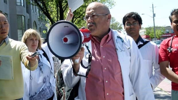 Dr. Paul Caulford, a family physician from Scarborough, speaks on a megaphone to protest proposed changes to health care for refugees and refugee claimants.