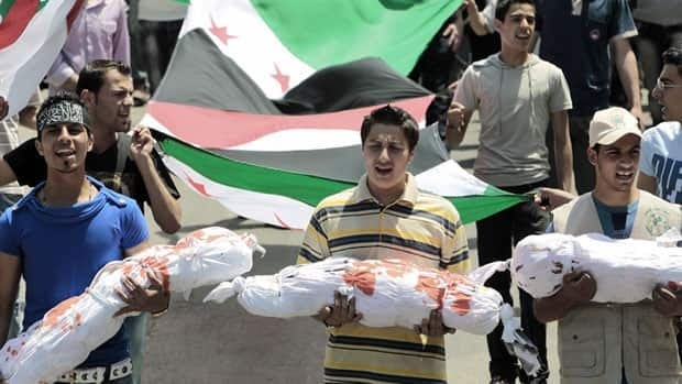 Lebanese protesters in Tripoli carry mock dead bodies during a demonstration against last week's massacre of more than 100 villagers in Syria.