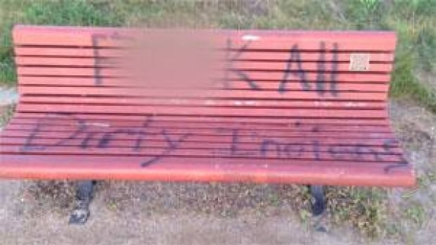 A park bench in Saskatoon was tagged with racist graffiti. This photo has been altered.