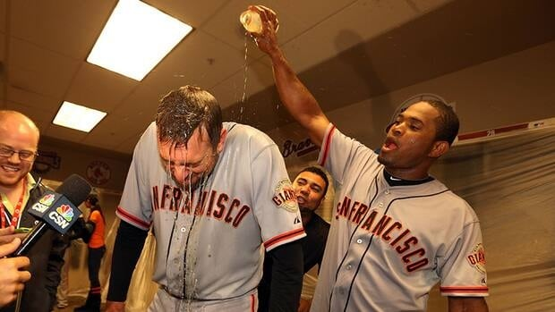 In this photo, San Francisco Giants' Santiago Casilla pours gatorade on teammate Jeremy Affeldt as they celebrate in the locker room following Game Five of the National League Division Series. Affeldt will be staying with the Giants for three more years.