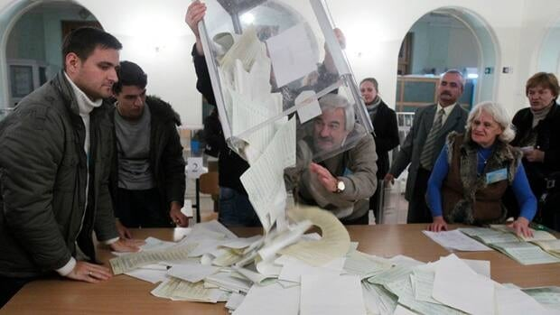 Members of a local electoral commission empty a ballot box at a polling station on Sunday in Kiyv, Ukraine.