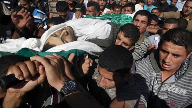Palestinians carry the body of Suliman al-Garah during his funeral in Khan Younis in the southern Gaza on Sunday. Israel said the Hamas militant was killed in an airstrike as he was attempting to fire a rocket from the Gaza Strip. A separate Palestinian salvo struck a southern Israeli city, forcing an Alberta politician to flee.