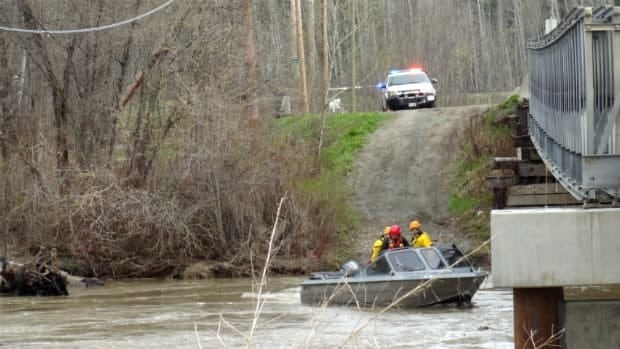 Search and rescue personnel comb the Willow River near Prince George, B.C., searching for a woman who was thrown into the water Sunday afternoon after her jetboat capsized.