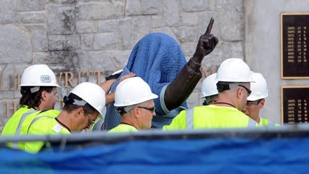 Penn State Office of Physical Plant workers cover the statue of former football coach Joe Paterno near Beaver Stadium on July 22 to prepare for its removal.