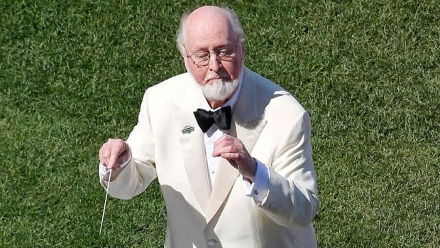 Composer John Williams, seen conducting the Boston Pops at Fenway Park before a baseball game in 2012, will return to score the next Star Wars film.