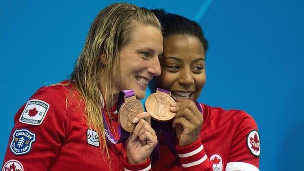 Canada's Emilie Heymans and Jennifer Abel show off their bronze medal on the podium after the women's synchronised 3-metre springboard final Sunday at the London Olympics.