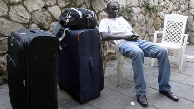 South Sudanese refugee Samuel Akue sits next to suitcases he purchased in a market in south Tel Aviv in preparation for his deportation from Israel.