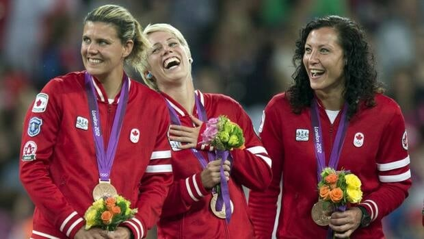 Canada women's soccer players Christine Sinclair, (left to right) Sophie Schmidt and Melissa Tancredi smile on the victory podium after being presented with their Bronze medals at the Olympic Games in London on Thursday August 9, 2012.