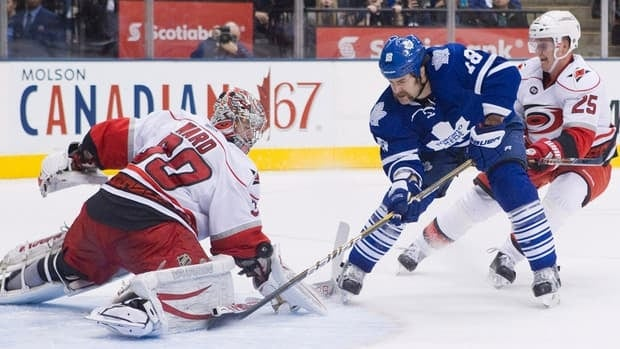 Carolina Hurricanes goaltender Cam Ward (left) stops Toronto Maple Leafs' Mike Brown (centre) as Hurricanes' Joni Pitkanen skates in during the second period in Toronto on Tuesday.
