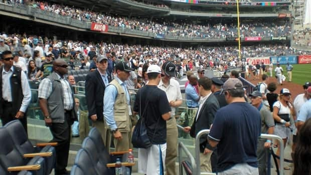 Prime Minister Stephen Harper, in the white shirt and khakis, signs an autograph for a baseball fan Sunday at Yankee Stadium. Harper was on a private weekend getaway with his family, his office said Tuesday.