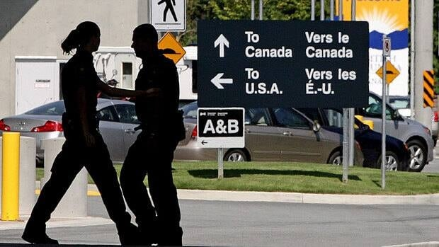 Canadian border guards are silhouetted as they replace each other at an inspection booth at the Douglas border crossing on the Canada-U.S. border on Aug. 20, 2009. A pilot project involving the inspection of truck cargo entails U.S. Customs and Border Protection officers working on the Canadian side of the border in Fort Erie, Ont. and Surrey, B.C.