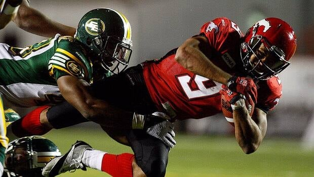 Eskimos' Simoni Lawrence, left, tackles Stampeders' Jon Cornish in the second half Friday. Cornish rushed for 180 yards, including 131 in the first half, on 20 carries.