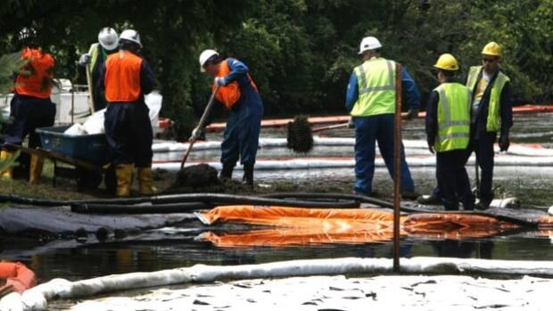 Crews clean up oil from a ruptured pipeline owned by Enbridge near booms and absorbent materials where Talmadge Creek meets the Kalamazoo River in Marshall Township, Mich., in July 2010.