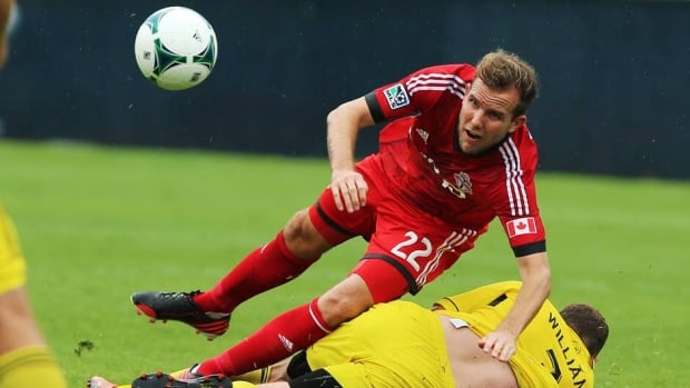Toronto FC's Jeremy Brockie, left, tumbles over Columbus Crew's Josh Wiliams, right, during the first half in Toronto on Saturday.