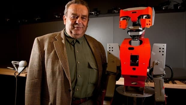 University of Ottawa scientist Emil Petriu is shown with a robot in his lab. Petriu and his colleagues are replacing the robot's mechanical parts with more human-like parts they are designing.